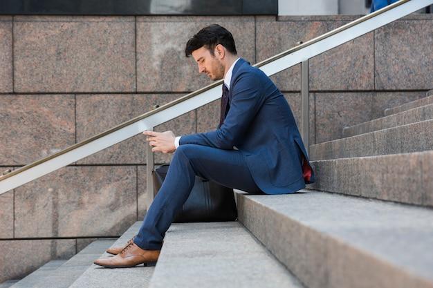 ビジネスマン、ステップ、スマートフォンを使用して