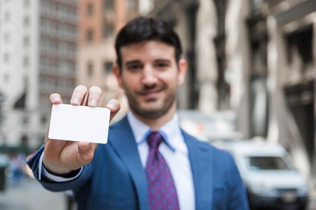 訪問カードを示すぼんやりしたビジネスマン