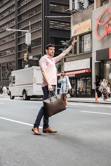 Человек приветствует такси на дороге