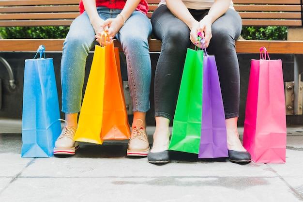 ショッピングバッグでベンチに座っている女性