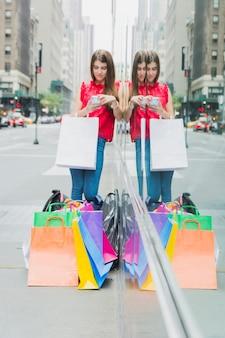 ストリートにショッピングバッグを持つ若い女性