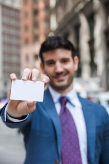 ビジターカードを示すぼんやりした実業家