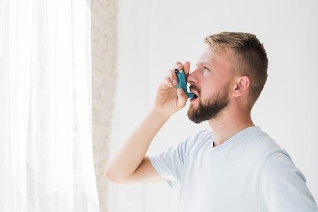 吸入器を使っている男