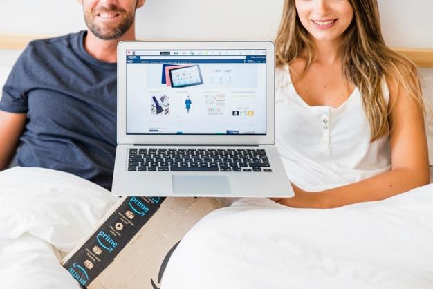 幸せな男性と女性のベッドでノートパソコンを見せる