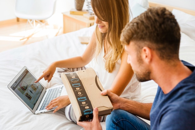 Женщина, показывая на ноутбук рядом с человеком с отправкой