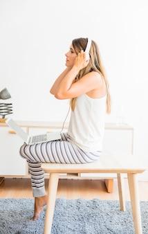 ノートパソコンとヘッドフォンで座っている女性