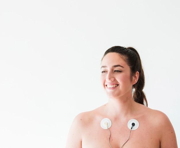 身体に電極を持つ若い笑顔の女性