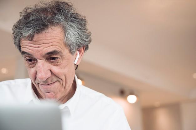 Улыбаясь старший бизнесмен, глядя на ноутбук
