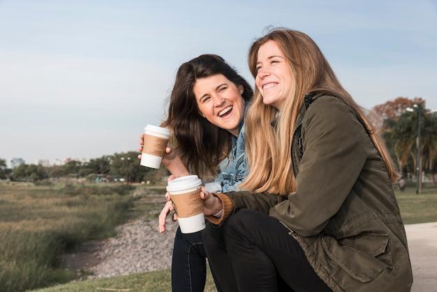 自然の背景でコーヒーを飲む女性
