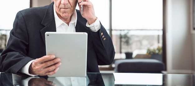 オフィス、デジタルタブレットを見て携帯電話で話す男のクローズアップ