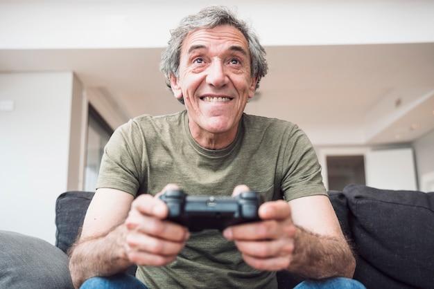 Улыбаясь старший мужчина, сидя на диване, наслаждаясь играть в видеоигру