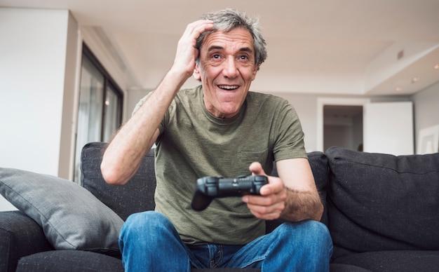 Счастливый старший мужчина, играющий в видеоигры дома