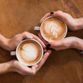木製のテーブルにコーヒーのカップを持っている女性