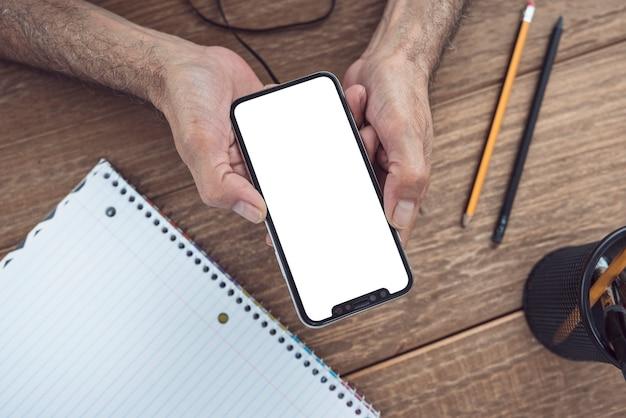 木製の机の上に白いスクリーンで携帯電話を持っている男の手のオーバーヘッドビュー