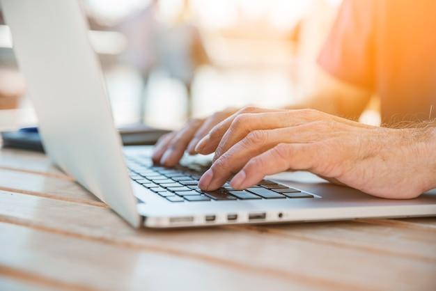 木製の机の上にノートパソコンで入力している男の手のクローズアップ