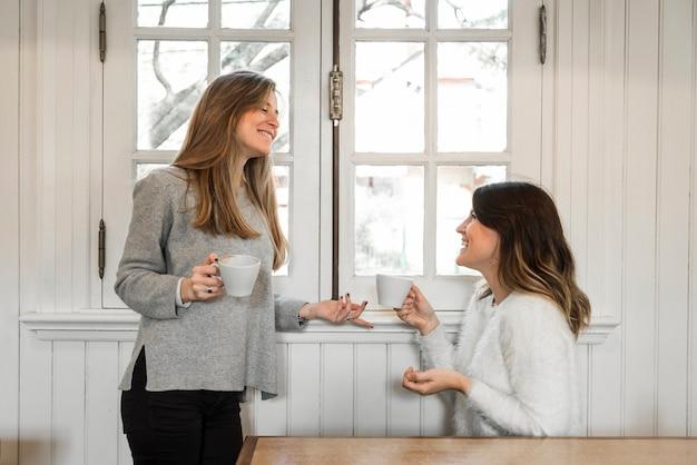 女性はコーヒーを飲み、窓の近くで話す