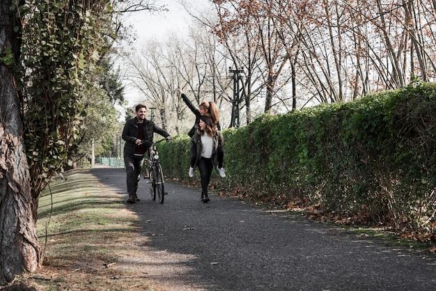 Люди, идущие с велосипедом в парке