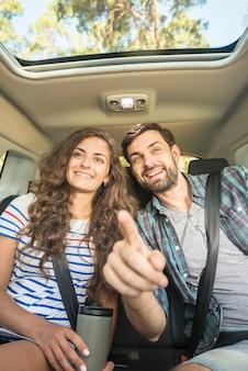 Молодая пара в автомобильной поездке