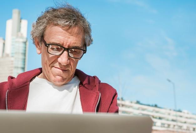 Крупным планом старшего человека, используя ноутбук с белым экраном