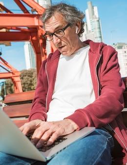 屋外でラップトップを使用してベンチに座っている高齢者