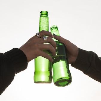 手でビールのボトルをつまむ