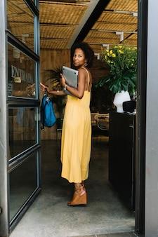 魅力的な若い女性は、バッグとラップトップをレストランに入れて