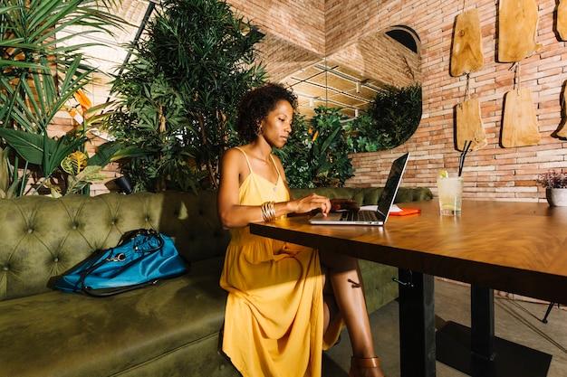 スタイリッシュな若い女性はラップトップを使用してレストランのテーブルに座ってカクテル