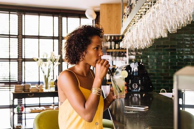 Вид сбоку молодая женщина, пить коктейль в бар счетчик