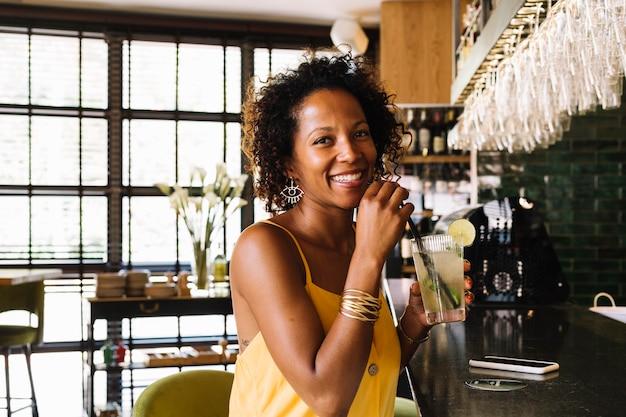 Счастливый молодая женщина, сидя на барной стойке, проведение бокал коктейля в ресторане