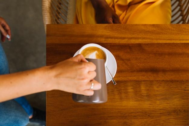 テーブル、カップ、ミルク、注ぐ、女の手のクローズアップ