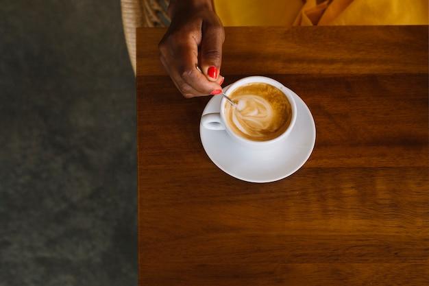 木製のテーブルにスプーンで熱いコーヒーをかき混ぜる女性