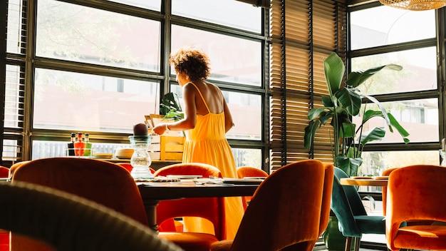 レストラン、窓のそばに立っている女性