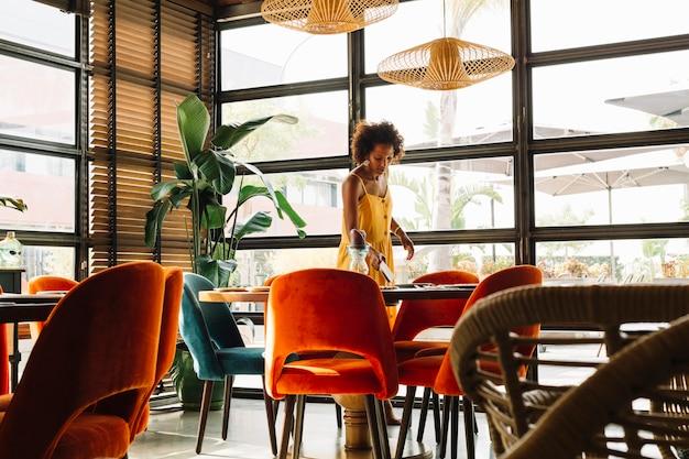 レストランでテーブルを並べ替える若い女性
