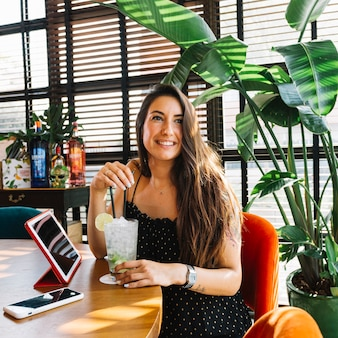 美しい若い女性をカクテルで笑顔にする。レストランのスマートフォンとデジタルタブレット