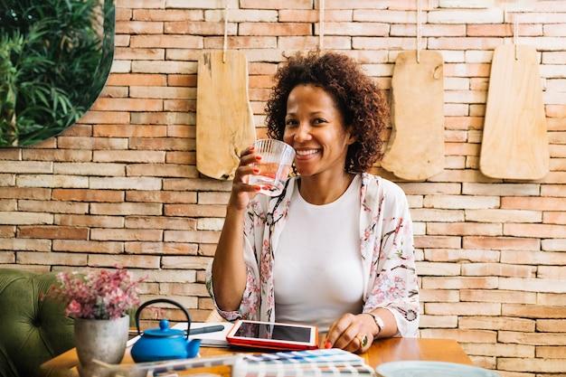 ジュースのガラスを飲む若い女性に笑顔