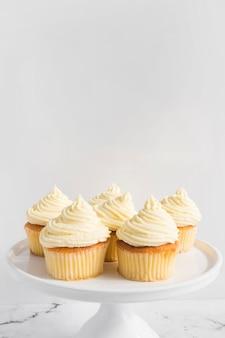 白い背景に対してケーキのスタンドにホイップクリームとカップケーキ