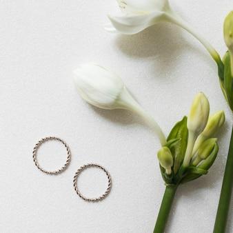 Обручальные кольца и свежий цветок с бутонами на белом текстурированном фоне