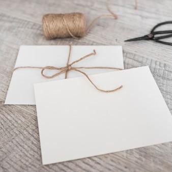 木製の背景に弦とはさみを持つ白い封筒