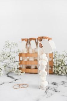 白い背景に空白のタグと結婚指輪とテストチューブでマシュマロ