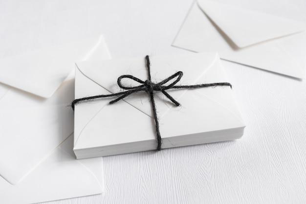 Обернутые подарочные коробки, связанные черной струной и конвертом на белом фоне