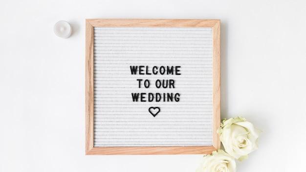 キャンドルと白い背景で結婚式のためのウェルカムフレームとローズ