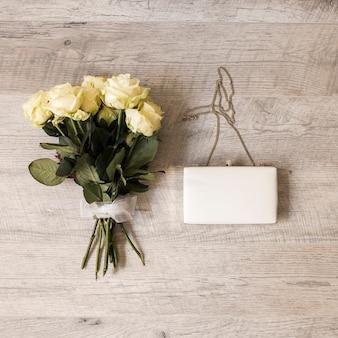 木製の背景にクラッチ付きの白いリボンで結ばれたバラの花束