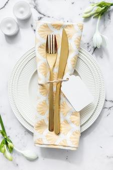 キャンドル;花、白いプレート、折り畳まれたナプキンとカトラリー、テクスチャ付きの背景