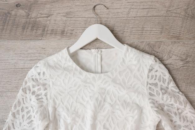 木製のテクスチャ付きの背景に対するコートハンガーの白いウェディングドレス