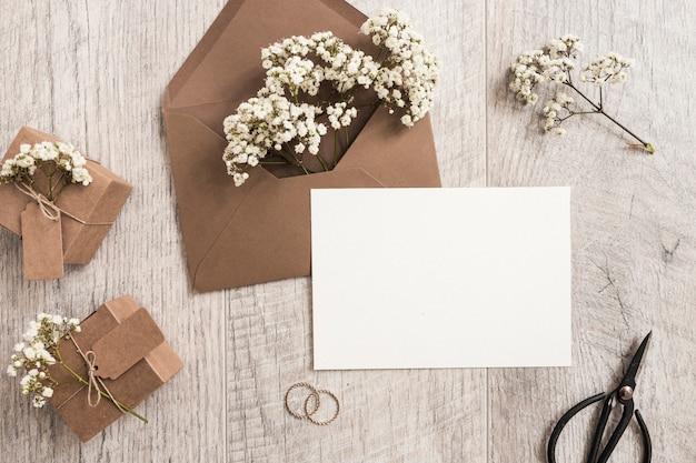 赤ちゃんの呼吸の花と茶色の封筒;ギフトボックス;結婚指輪;はさみと木製の背景に白いカード