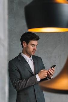 Молодой бизнесмен в костюмах с помощью мобильного телефона