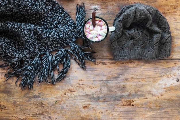 ホットチョコレートの近くのスカーフと帽子