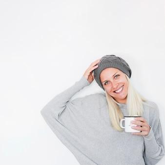 Веселая женщина с горячим напитком