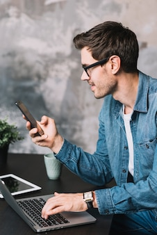 ラップトップでタイピングして携帯電話で見る若い男