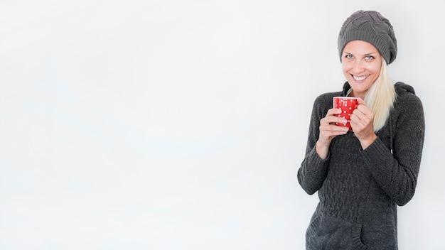 マグカップを着た暖かい服の陽気な女性